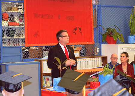 Sen. Charles Perry addresses WSD graduates at the Roach Unit while (right) Principal Erika Moore listens.