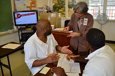 WSD teacher Jo Smith discusses a Workplace Skills assignment with Ellis Unit offenders in Huntsville during July. The Ellis Unit was one of 46 sites offering new summer school courses within the Texas Department of Criminal Justice.