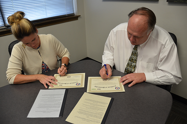 Megan Thornton, Vice President, Human Resources-Clean Scapes, and Windham School District Superintendent, Dr. Clint Carpenter, sign a collaboration agreement to help reduce the recidivism rate by vocational students gaining employment with their company.